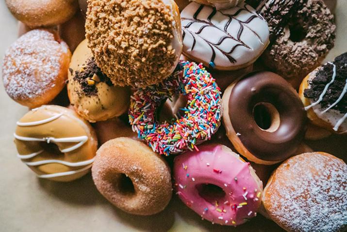 En hög med donuts med strössel och glasyr