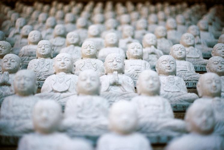 Stenstatyer som sitter uppradade som konferensdeltagare eller publik